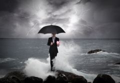 Business man under an umbrella in the sea